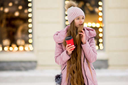 A girl in a pink warm jacket and hat with 