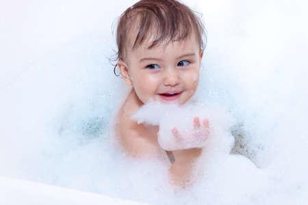 cute baby is swimming in bath in a foam