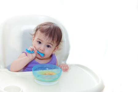 sittting: baby eating in the kitchen on the sittting on the table