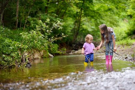 2 つの素敵な女の子は、木で遊ぶ。2 人の姉妹は、新鮮な空気の時間を過ごします。 写真素材 - 81793546