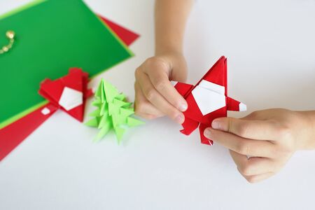 Santa Claus of origami a fir-tree of origami from paper on a white background. Lesson of origami Stock Photo