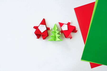 Santa Claus of origami a fir-tree of origami from paper on a white background. Hands of the child put a fir-tree.