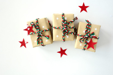 The Christmas gifts packed into a beige kraft paper, strewed with red, white paper stars on the white background. Top View Flat Lay