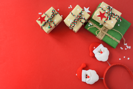 The Christmas gifts packed into a beige and green kraft paper, strewed with red, white paper stars on red background. Top View Flat Lay