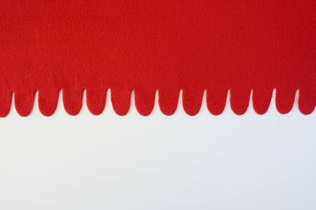 Red plaid from felt fabric on a white background. It is red a white background