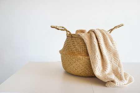 Wicker straw basket with a knitted plaid against the background of a white wall Stock Photo