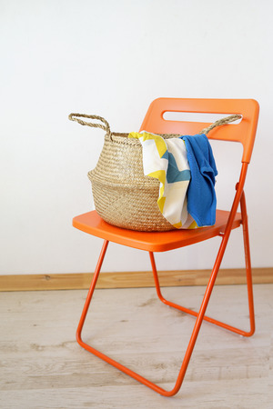 Wicker straw  basket with color linen against the background of a white wall