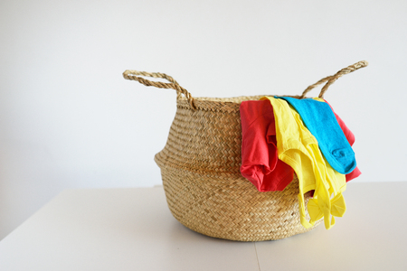 Wicker straw knitted basket with color linen against the background of a white wall