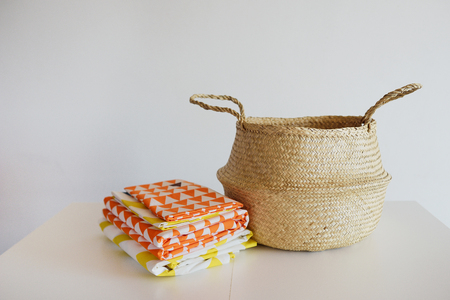 Bed multi-colored linen in a wicker basket against the background of a white wall on a white table.