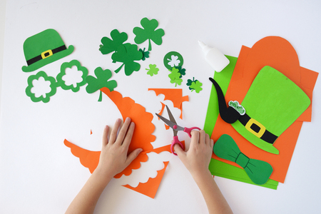 Top view.  Children's hands cut out a mask from paper for a St. Patrick's Day Standard-Bild - 93069422