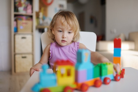 the little girl plays in the house multi-colored blocks