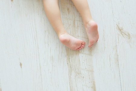 The childs legs on a floor. Top view. Nurseries of a foot.