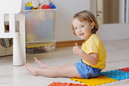 The kid plays with massage multi-colored puzzles.