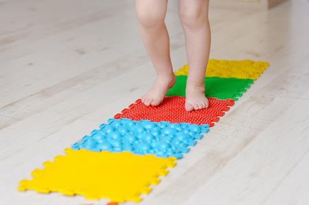 Baby foot massage mat. Exercises for legs on orthopedic massage carpet. Orthopedic massage puzzle floor mats for development of children.