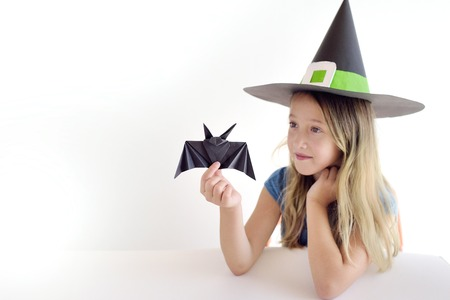 The girl plays in a self-made mask of witch for Halloween Stockfoto