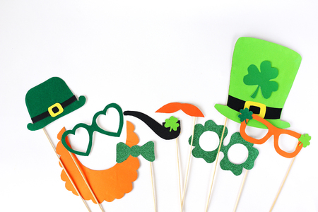 Festive masks for a St. Patricks Day on a white background. Fancy dress. Party Concept. Flat lay objects with paper craft on white wallpaper at home office desk with copy space.