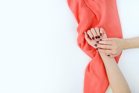 Le mani della ragazza con una bella manicure rossa tengono un tessuto di colore corallo.