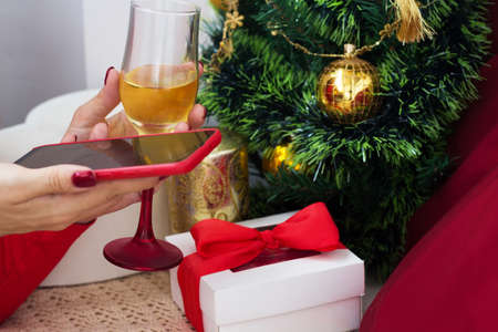 Christmas online congratulations. Holiday video meeting with social distance. Woman chatting with friend using smartphone.