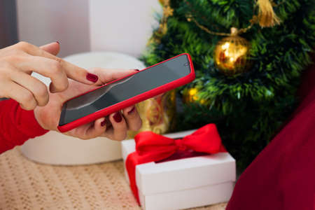 Online Christmas shopping. Woman buying gifts with smartphone. Presents order. Holiday video chat with freinds.