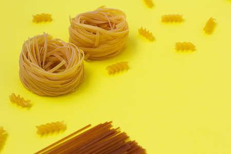 Buckwheat and whole wheat spaghetti. Uncooked macaroni and tortellinion yellow background. Different pasta type.