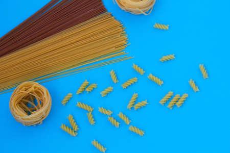 Uncooked corkscrew macaroni on blue background. Buckwheat spaghetti. Tortellini from white wheat, different pasta type