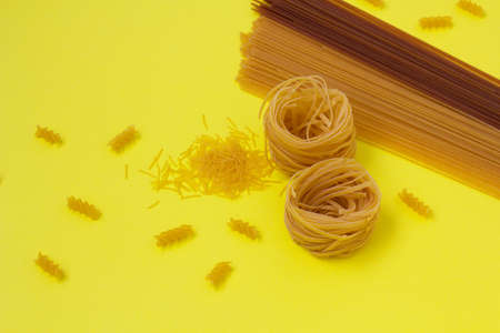 Buckwheat and whole wheat spaghetti. Uncooked corkscrew macaroni and tortellini on yellow background. Different pasta Фото со стока