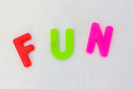 Colorful letters on white background. Kids plastic toy, learning alphabet and english words in language school. Text fun Фото со стока