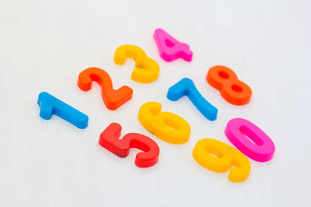 Colorful plastic numeral on white background. Learning numbers with fridge magnets. Arithmetic education in school Фото со стока