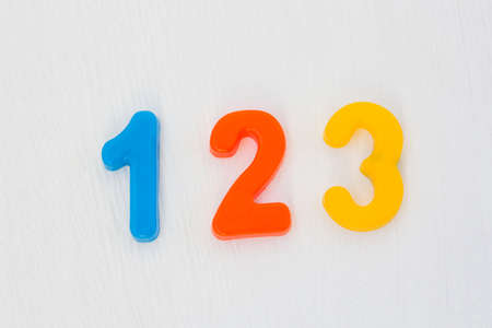 Colorful plastic numeral one, two, three on white background. Learning numbers and counting with fridge magnets