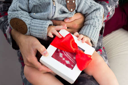 Give Cristmas presents. Family Gift exchange on holiday. Baby sitting on father