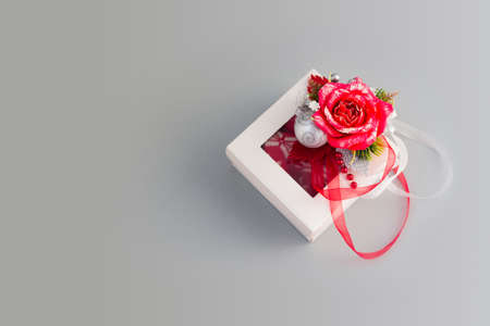 Top view of white gift box with red rose and bauble on silver background. Christmas Horizontal banner with copy space