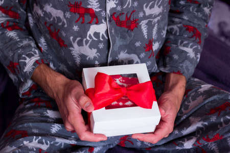 Christmas loneliness. Man in comfy pajamas opening present. Quarantine Holiday celebration. New Year gift delivery Фото со стока