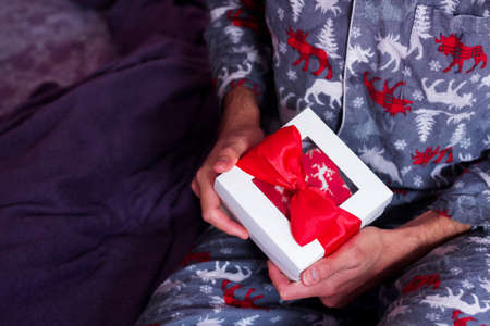 Man sitting in comfy pajamas opening Christmas present. Home holiday celebration. Classic white gift box with red bow