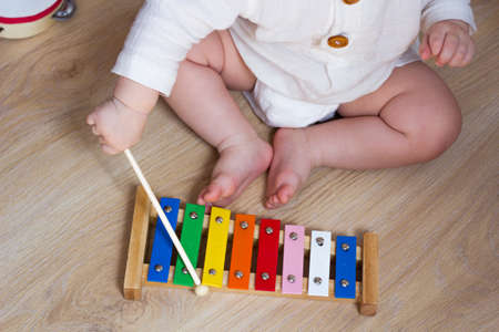 Baby playing xylophone, tambourine. Kids musical instrument toy. Little child musician