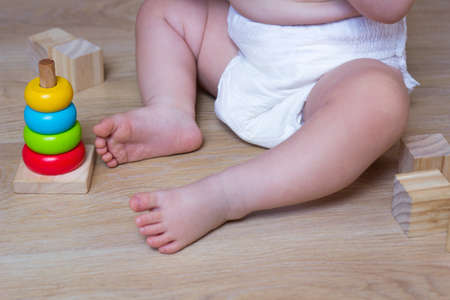 Infant playing with Ecological toys made from natural material. Kids Wooden Blocks and baby pyramid Фото со стока