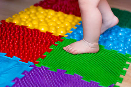 Kids Rubber play floor. Orthopedic massage mat, baby foot on massaging puzzle rug. Barefoot boy walking. First step