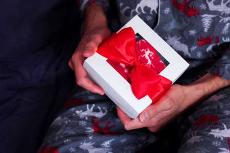 Christmas during quarantine. Man sitting in comfy pajamas alone and opening present. Stay Home holiday celebration. New year gift delivery Фото со стока