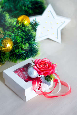 White gift box with red rose and bauble. Greeting card with Christmas tree. New year decoration Фото со стока
