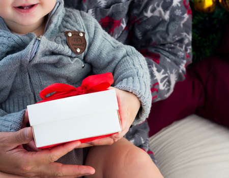 Baby giving gifts. Give Cristmas presents on holiday. Gift exchange with family