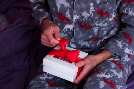 Christmas during quarantine. Man sittingalone and opening present. Stay Home holiday celebration. Gift delivery service