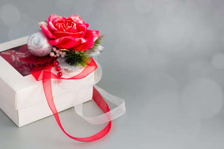 White gift box with red rose and ribbons on silver background. Horizontal banner with copy space for text. Christmas Holiday greeting card Фото со стока