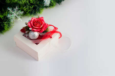 White gift box with red rose and ribbons on white background. Horizontal banner with copy space for text. Christmas tree garland Holiday greeting card Фото со стока