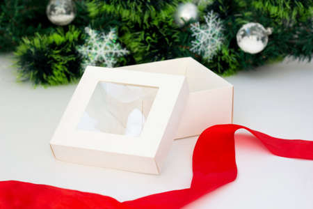 Empty White gift box with red ribbon on white background. Christmas tree garland. Holiday Horizontal template Фото со стока