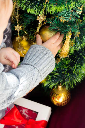 Baby boy decorating the Christmas tree, toddler holding baubles in hand