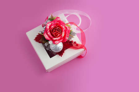 Christmas card with copy space for text. Top view of White gift box with red rose and bauble on pink background Фото со стока