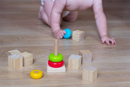 Baby playing with Ecological toys made from natural material. Kids Wooden Blocks and pyramid