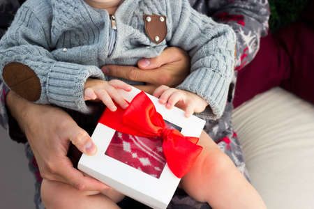 Baby boy gets Cristmas presents. Kid holding gift with red ribbon Фото со стока