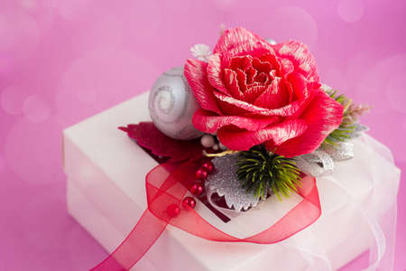 Female Christmas greeting card with copy space for text. White gift box on pink background with bokeh Фото со стока