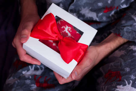 Merry Christmas greeting card. Give presents concept. New year surprise. Man with gift box in his hand