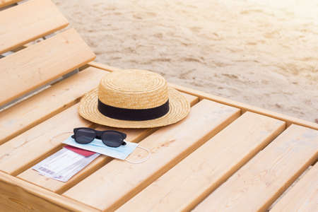 Safe Summer vacation. Sunglasses, mask and hat. Rest on the beach
